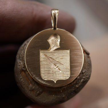 Gravure héraldique en creux sur une médaille or jaune 18k