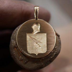 Médaille en or gravée main. Blason et heaume