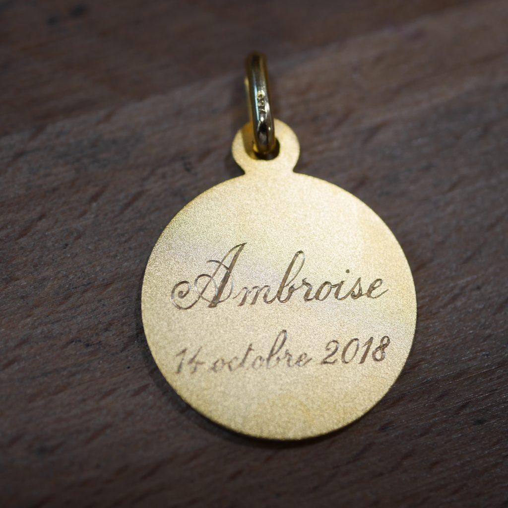 Gravure prénom et date sur une médaille de baptême